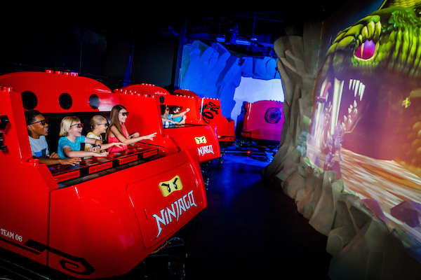 LEGOLAND Beach Retreat - young children playing a Ninjago virtual video game in a red gaming car.