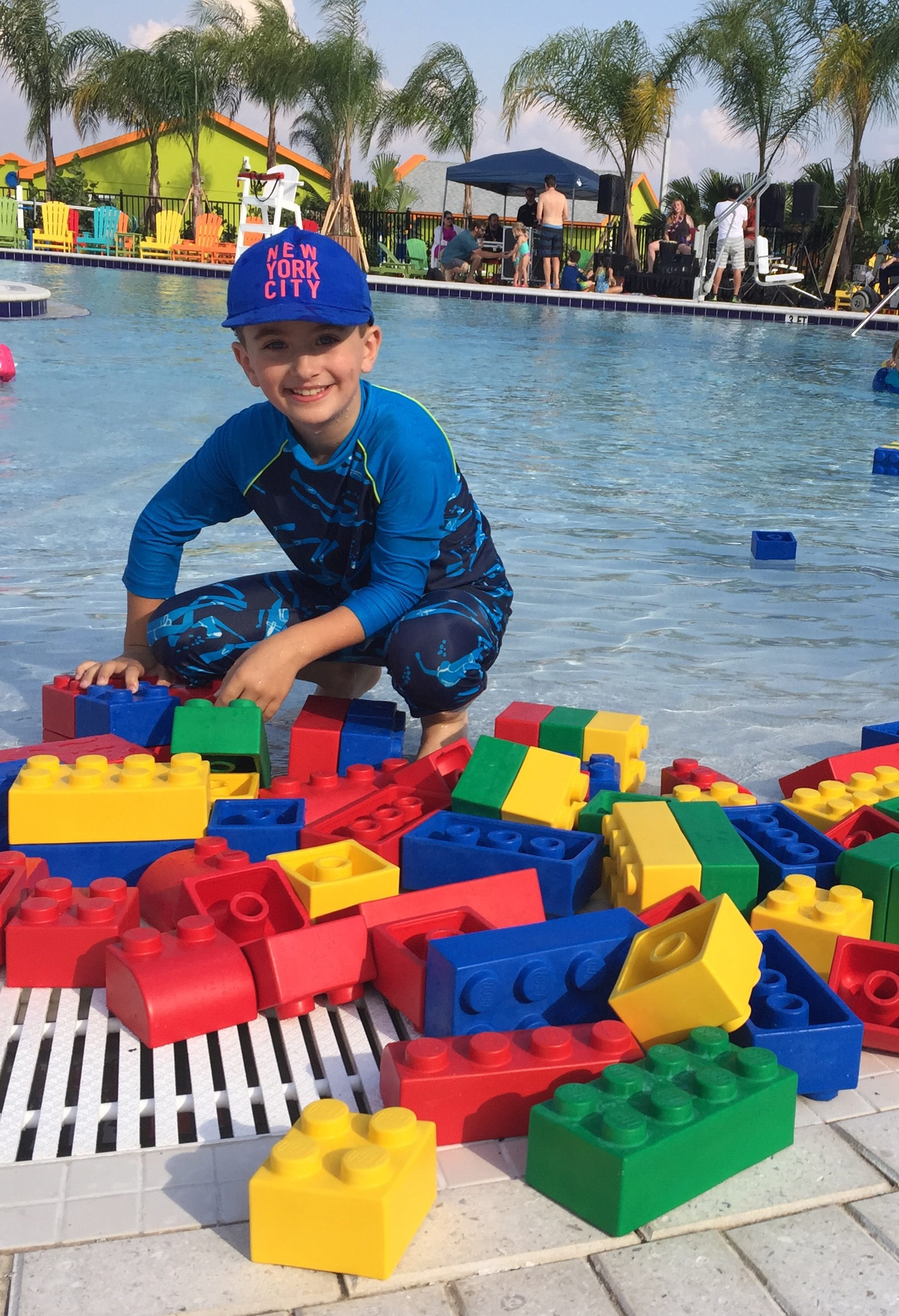 LEGOLAND Beach Retreat - Young boy by a pool with a pile of Lego blocks.